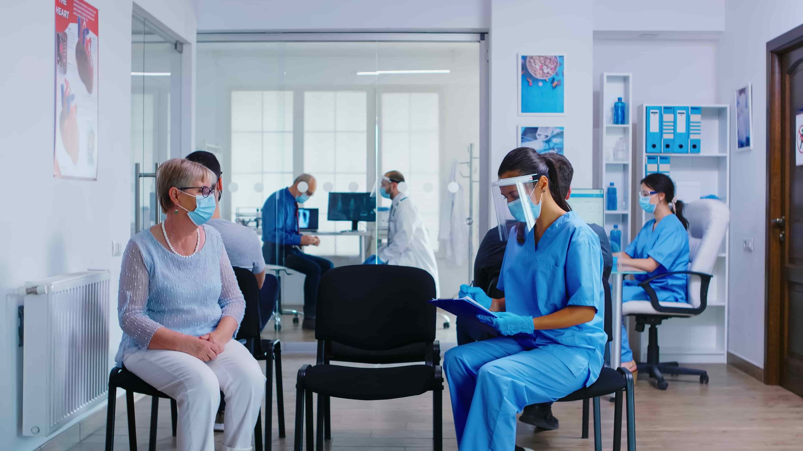 LPN nurse in clinic taking notes on patient